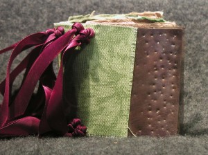 Wee book exterior w/ fabric and copper cover. Pages held in with ribbon. Not the best color choices for this project.