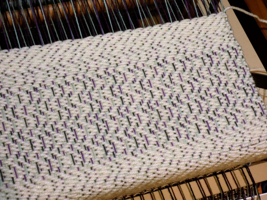 Creating a sampler with the existing warp. The white yarn is scrap acrylic.